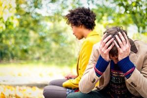 Couple sitting outside, upset